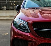 röd prestigebil i parkeringsplatsen av byggnaden royaltyfri fotografi