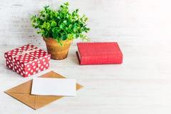Röd prickig gåvaask, tomt kort, kraft kuvert, röd bok och en grön blomma i en lantlig keramisk kruka Vit träbakgrund, snut Royaltyfri Fotografi