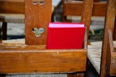 Röd psalmbok på stol fotografering för bildbyråer