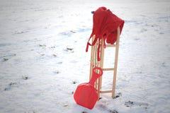 Röd pulka och varm byxa i snölandskap royaltyfria bilder