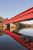 Röd räknad bro med reflexion i vatten Arkivbild