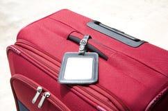 Röd resväska med etiketten royaltyfri bild