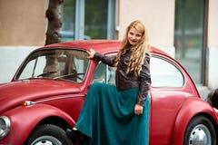 Röd retro bil nära blond flicka med lång krullning arkivfoto