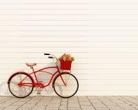 Röd retro cykel med korgen och blommor framme av den vita väggen, bakgrund Royaltyfria Foton