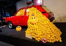 Röd Retro tappningbil som fylls med gula färgbollar royaltyfri foto