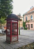 Röd retro telefon-ask i gammal stad Royaltyfri Bild