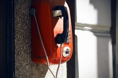 Röd retro telefon för gata som är tillgänglig för alla arkivfoton
