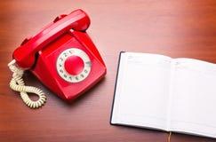 Röd retro telefon med anteckningsboken Arkivbilder