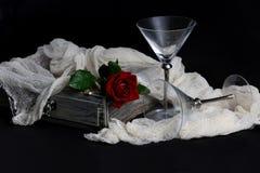 Röd ros, diamantcirkel och vinexponeringsglas på en svart bakgrund royaltyfri bild