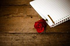Röd ros i anteckningsbok på trä Arkivfoto