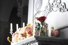 Röd ros i en exponeringsglasflaska på en gammal spis royaltyfria foton