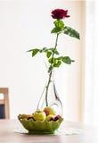 Röd ros i en vas och en platta med bär och frukter Royaltyfria Foton