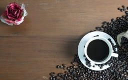 Röd ros med koppen för vitt kaffe på tabellen Arkivbild