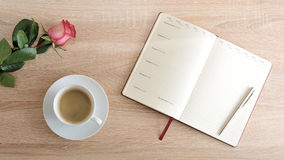 Röd ros och en kopp kaffe och en dagbok med dagar av veckan Royaltyfria Foton