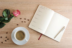 Röd ros och en kopp kaffe och en dagbok med dagar av veckan och Royaltyfria Bilder