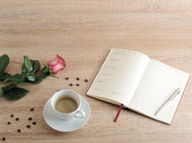 Röd ros och en kopp kaffe och en dagbok med dagar av veckan och Royaltyfri Fotografi