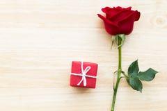 Röd ros och gåva för valentin på den wood tabellen Royaltyfria Bilder
