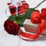 Röd ros och gåvor arkivfoton