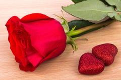 Röd ros och två hjärtor på ljus träbakgrund fotografering för bildbyråer