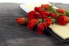 Röd ros på en anteckningsbok och en blyertspenna Arkivfoto