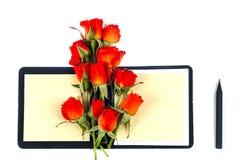 Röd ros på en anteckningsbok och en blyertspenna Arkivbild