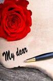 Röd ros på gammalt woodlovebokstavsbegrepp på den wood tabellen Royaltyfri Fotografi
