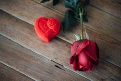 Röd rosblomma på trägolv i valentin dag Arkivfoton