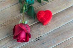 Röd rosblomma på trägolv i valentin dag Fotografering för Bildbyråer