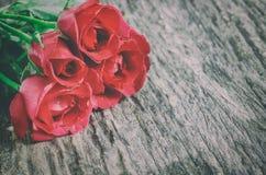 Röd rosblommabukett på träbakgrund med tappningsignal Arkivfoton