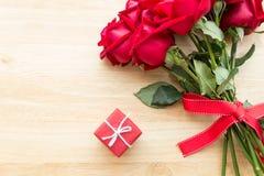 Röd rosbukett med röd gåva på den wood tabellen Arkivbild
