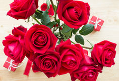 Röd rosbukett med röd gåva på den wood tabellen Arkivfoton