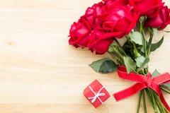 Röd rosbukett med röd gåva på den wood tabellen Arkivbilder