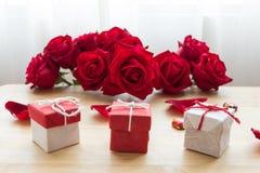 Röd rosbukett med röda gåvor på den wood tabellen Royaltyfria Bilder