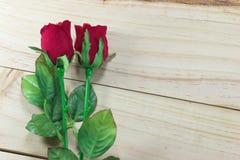 Röd rosgarnering för valentin dag på wood bakgrund Fotografering för Bildbyråer