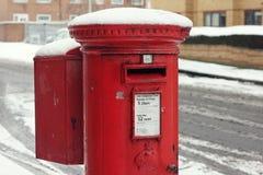 Röd Royal Mail Postbox i snön, UK Arkivbild
