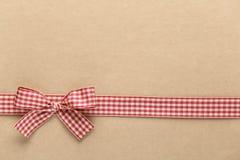 Röd rutig bandpilbåge på brunt papper Royaltyfri Bild