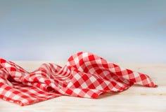Röd rutig bordduk på trätabellen, ferietapet fotografering för bildbyråer