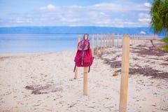 Röd ryggsäck på staketet på den exotiska tropiska stranden Royaltyfri Foto