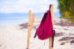 Röd ryggsäck på staketet på den exotiska tropiska stranden Royaltyfri Bild