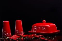 Röd salt-källare, peppar-ask och smör på darckbakgrund av Cristina Arpentina Arkivfoto