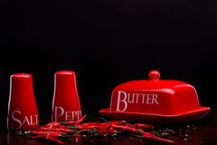 Röd salt-källare, peppar-ask och smör på mörk bakgrund av Cristina Arpentina Royaltyfri Fotografi