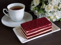 Röd sammetkaka och en kopp te Royaltyfri Bild