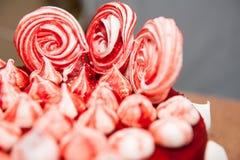 Röd sammetkaka som dekoreras med vita och röda marängar, vit bakgrund, slut, velor, idé för en ferie, symbol för kafé Royaltyfri Bild
