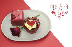 Röd sammetmuffin, gåva och rosknopp som äter middag tabellinställningen med förälskelsemeddelandet för valentindag Arkivfoton
