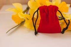 Röd sammetpåse med gula blommor på en vit bakgrund, kopieringsutrymme fotografering för bildbyråer