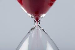 Röd sand i ett timglas som är horisontal royaltyfri bild