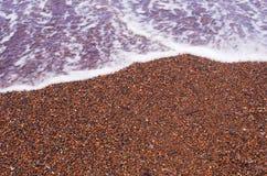 Röd sand på stranden av Santorini, Grekland fotografering för bildbyråer