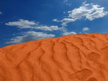 Röd sandkulle i öknen krusningar i sanden med molnen royaltyfri foto