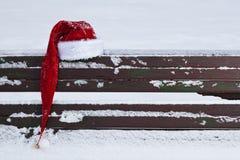 Röd Santa Claus hatt på snö täckt bänk Fotografering för Bildbyråer