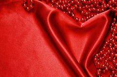 Röd satäng och pärlor Arkivbilder